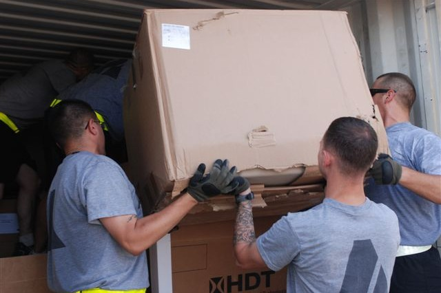 Soldiers from the Intel and Sustainment Company, Division Headquarters and Headquarters Battalion, 1st Infantry Division pack a box of equipment into a connex in preparation for the unit's participation in the Responsible Drawdown of Forces.