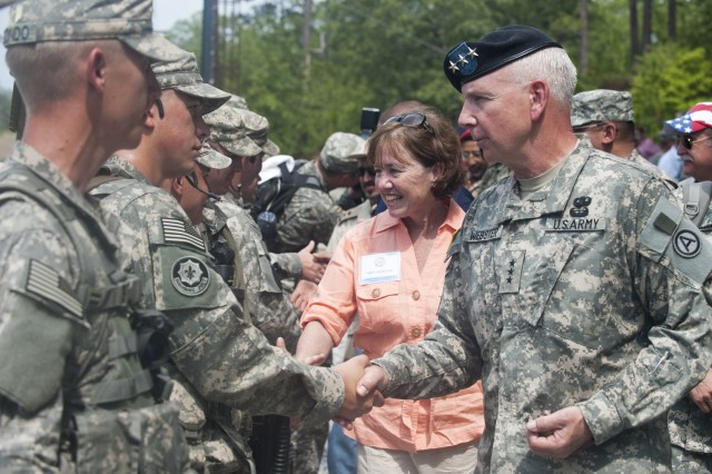 """Lt. Gen. William G. Webster, Third Army/U.S. Army Central commanding general, and Mrs. Kimberly Webster greet and thank Soldiers at the Ranger Training Brigade, after they participated in the """"Rangers in Action"""" demonstration at Hurley Hill, Fort Benning, Ga., Aug. 3. The event highlighted the third day of the Land Forces Symposium with senior leaders from more than a dozen countries in U.S. Central Command's area of responsibility."""