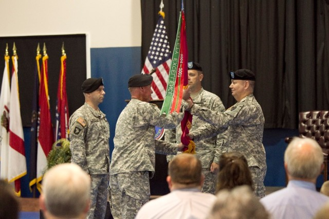Lt. Col. Randall DeLong gives the Anniston Defense Munitions Center flag to Blue Grass Army Depot Sgt. Maj. Paul Baxter after receiving it from BGAD Commander Col. Brian Rogers. Pictured at left is outgoing commander Lt. Col. Duncan MacMullen.