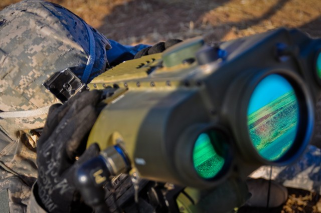 Specialist Justin Duff, a forward observer with Headquarters and Headquarters Company, 2nd Heavy Brigade Combat Team, 3rd Infantry Division, and watches as rounds fired from a Paladin Howitzer hit their targets during a Combined Arms Live Fire Exercise, in Ninewa province, northern Iraq, July 24.