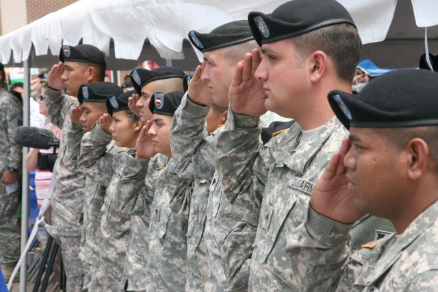 FORT CARSON, Colo. - Soldiers present arms during the national anthem moments prior to taking the oath of citizenship and officially becoming U.S. citizens July 29 to conclude the Army Community Service birthday celebration in the ACS parking lot.