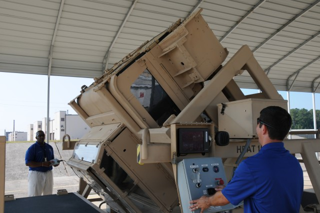 Ernest Everett, 3rd ID COMET instructor, master driver and HEAT trainer, operates control box for the HEAT training simulator as Ramos Efrain, COMET team instructor and HEAT trainer monitors Soldiers in the simulator via the video screen, July 30.