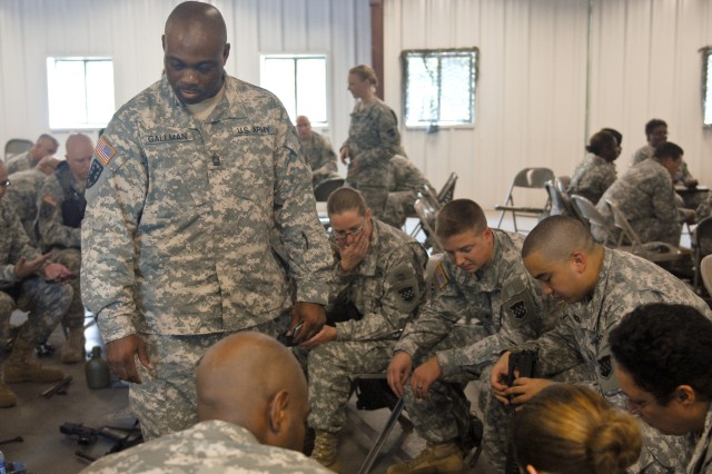 Master Sgt. David Gallman looks on as Soldiers from Headquarters, Headquarters Company, 99th Regional Support Command disassemble their M16/A2 rifles during Preliminary Marksmanship Instruction at Joint Base McGuire-Dix-Lakehurst on August 5.