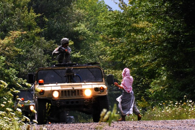 FORT DRUM, NY--Sgt. Jodie Brassard, of Allendale. NY, dressed as an Afghan national, attempts to distract a Humvee crew from B Company, 427th Brigade Support Battalion during the company's blank-fire convoy exercise on Fort Drum July 28. Brassard and the rest of the 427 BSB were on Fort Drum to participate in the 27th Infantry Brigade Combat Team's annual training exercises