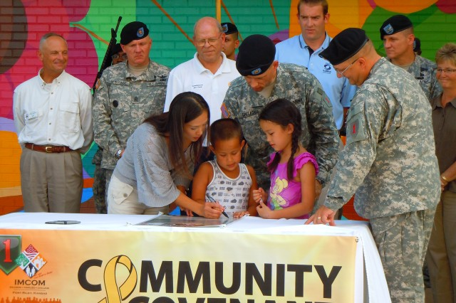 SALINA, Kan. - Spc. Harold Gallagher, a Soldier with the Combat Aviation Brigade, 1st Infantry Division, his wife, Tomomi Gallagher, and their two children, Sara, 7, and Andrew, 5, sign the Saline County Army Community Covenant Aug. 4 in Salina, Kan., as members of the Fort Riley command group, CAB Soldiers, Saline County commissioners and community members look on. This covenant signing was the first between Saline County and Fort Riley, Kan., and marks the official start of the partnership between the two. The Army Community Covenant signing publically demonstrates the CAB and Saline County's pledge to support each other. This signing took place before the start of the Tri-Rivers Fair parade in downtown Salina, Kan. Army Community Covenant signings will take place across the Central Flint Hills region in Kansas through October.