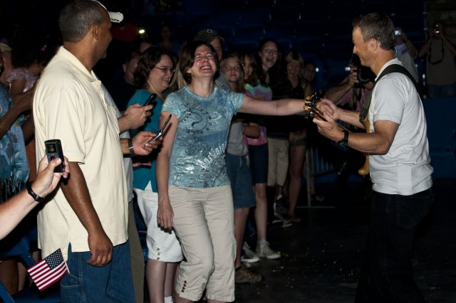 Gary Sinise pulls a fan from the audience to dance during a performance at the Crown Coliseum in Fayetteville, July 31.