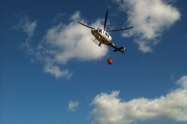 An Army-contracted helicopter fills heads out to drop  water on the wildfire at Makua Military Reservation, July 25. Staff from the Oahu Army Natural Resources Program assisted in directing the water bucket drops to help protect threatened and endangered species in the area.