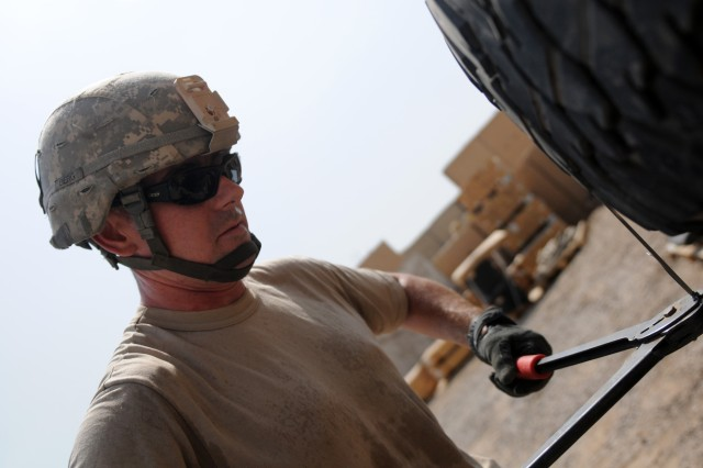 BAGHDAD - Sgt. Matthew Berg, an automated logistical specialist with Company B, Division Special Troops Battalion, 1st Armored Division and a Mobile, Ala., native, makes sure the binding around used tires is taut Aug. 3 at Camp Liberty, Iraq. These tires, along with other unserviceable gear, will be taken to a yard where they will be retrograded out of Iraq.   (U.S. Army photo by Cpl. Daniel Eddy, 196th MPAD, USD-C)
