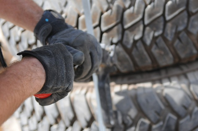 BAGHDAD - Sgt. Matthew Berg, an automated logistical specialist with Company B, Division Special Troops Battalion, 1st Armored Division and a Mobile, Ala., native, tightens a metal strap Aug. 3 to ensure used tires will not fall off during transport out of Camp Liberty, Iraq. These tires, along with other unserviceable gear, will be taken to a yard where they will be retrograded out of Iraq.(U.S. Army photo by Cpl. Daniel Eddy, 196th MPAD, USD-C)