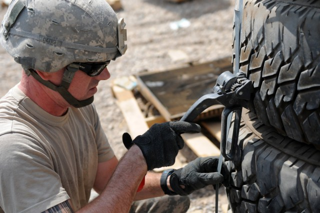 BAGHDAD - Sgt. Matthew Berg, an automated logistical specialist with Company B, Division Special Troops Battalion, 1st Armored Division and a Mobile, Ala., native, tightens a metal strap around tires Aug. 3 to prevent them from shifting while they are transported for disposal out of Camp Liberty, Iraq. These tires, along with other unserviceable gear, will be taken to a yard where they will be retrograded out of Iraq. (U.S. Army photo by Cpl. Daniel Eddy, 196th MPAD, USD-C)