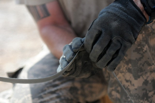 BAGHDAD - Sgt. Matthew Berg, an automated logistical specialist with Company B, Division Special Troops Battalion, 1st Armored Division and a Mobile, Ala., native, secures used tires together Aug. 3 at Camp Liberty, Iraq. Once secured, the tires will be loaded on to a truck and driven to a yard where unserviceable equipment is disposed of properly.(U.S. Army photo by Cpl. Daniel Eddy, 196th MPAD, USD-C)