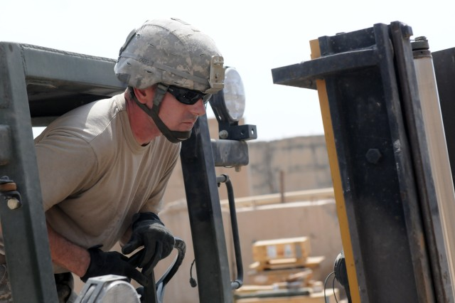 BAGHDAD - Sgt. Matthew Berg, an automated logistical specialist with Company B, Division Special Troops Battalion, 1st Armored Division and a Mobile, Ala., native, ensures he hooks the correct wooden pallet with a forklift Aug. 3 at Camp Liberty, Iraq. The unserviceable gear on the pallets will be retrograded out of Iraq.   (U.S. Army photo by Cpl. Daniel Eddy, 196th MPAD, USD-C)