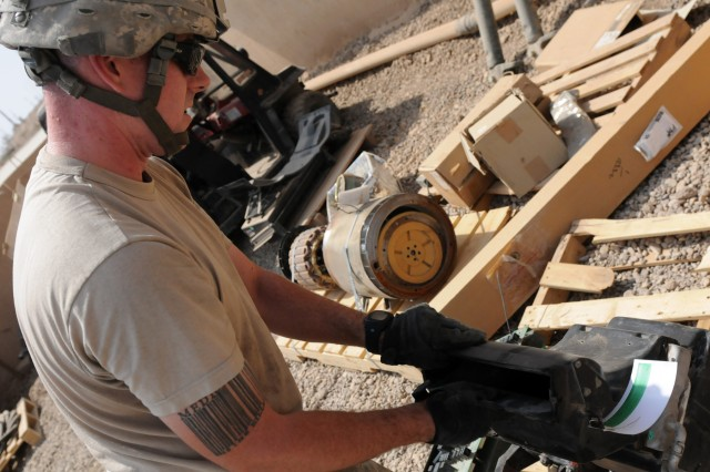 BAGHDAD - Sgt. Matthew Berg, an automated logistical specialist with Company B, Division Special Troops Battalion, 1st Armored Division and a Mobile, Ala., native, inspects unserviceable gear Aug. 3 at Camp Liberty, Iraq. Berg is helping Co. B retrograde unnecessary equipment that has accumulated during its deployment.(U.S. Army photo by Cpl. Daniel Eddy, 196th MPAD, USD-C)