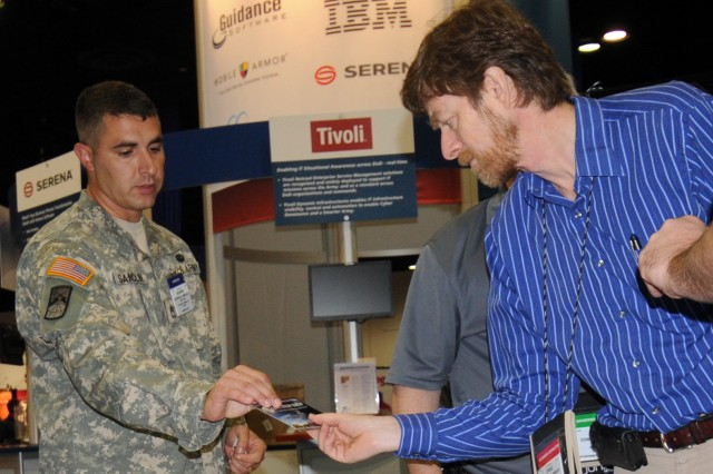 "Sgt. 1st Class George Sandlin passes information about information assurance to a visitor at the Army IA booth at the recent 2010 Armed Forces Communications and Electronics Association's ""LandWarNet"" conference in Tampa, Fla."