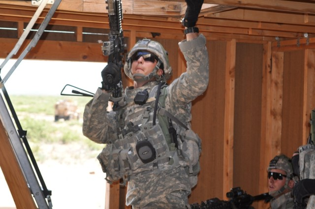 Before searching the rooftop a soldier prepares for enemy contact.
