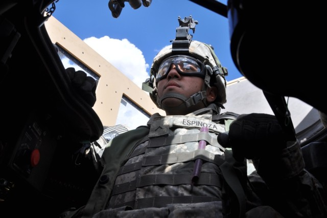 PV2 Julio Espinoza stands ready on the turret while conducting operations during the STX.