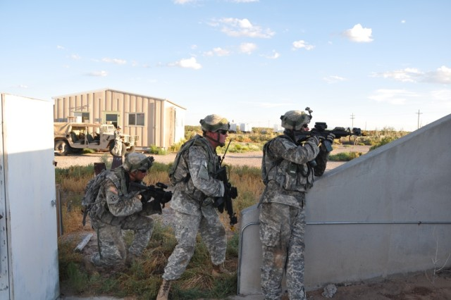 Soldiers from 2CAB stand watch over the breaching squad, after securing the building and engaging the insurgents.