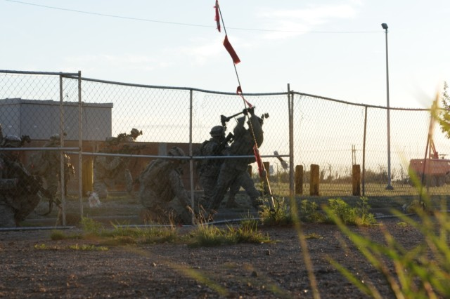Soldiers breach a fence on an objective, using an axe to sever the chain.