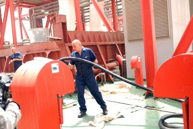 Turkish workers run fuel hoses across the deck of the Dogan Bey power ship to keep the generators filled and pumping to capacity.