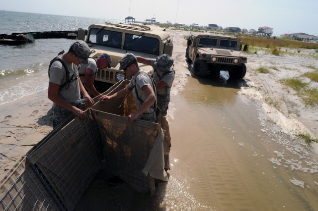 Soldiers from the Alabama National Guard build and maintain miles of barriers to protect Dauphin Island, Ala., beaches from the BP oil spill, July 23, 2010. More than 1,400 National Guard members are supported Operation Deepwater Horizon in four Gulf states.