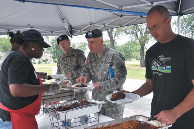 """Aberdeen Proving Ground commanders bid farewell to a group that has been the face of the installation for 51 years during a send-off for the U.S. Army Materiel Command Band at the Shore Park picnic area Aug. 2. Maj. Gen. Nick G. Justice, commander of APG and the U.S. Army Research, Development and Engineering Command, hosted the send off as a show of appreciation for the many years the band has served the installation. Justice was joined by Col. Orlando W. Ortiz, APG Garrison and deputy installation commander, installation and RDECOM Command Sgt. Maj. Hector Marin, and APG Garrison Command Sgt. Maj. Rodney Rhoades. Band Soldiers and Family members dined in the park pavilion along with invited guests. First Sergeant's Barbecue provided the food and refreshments. After the meal, Justice commended band members for consistent and positive representation of the installation, and surprised Sgt. Anthony Gentilo with an impact award. Gentilo, who sang the national anthem during the Armed Forces Appreciation festivities at Ripken Stadium in Aberdeen July 30, was awarded the Army Achievement Medal for his performance. Justice said Gentilo was even more impressive when he sang """"God Bless America"""" during the traditional seventh inning stretch. """"I could not believe the control he had over that crowd,"""" Justice said. """"More than a few people were in tears by the time he began the last crescendo. """"And that's what you bring to music in the Army,"""" he told the band members. """"You present the best view of the American Soldiers. We thank you so much and we wish you a fond farewell because I don't know how in the world we'll replace the AMC Band."""" Ortiz said that the surrounding community will miss the band as much as the installation. """"You should fully understand that you are greatly appreciated on this installation,"""" he said. """"It is because of your professionalism that you have the reputation that you do. You will always have a home here."""" Justice thanked Mary Jane Jernigan, president of"""