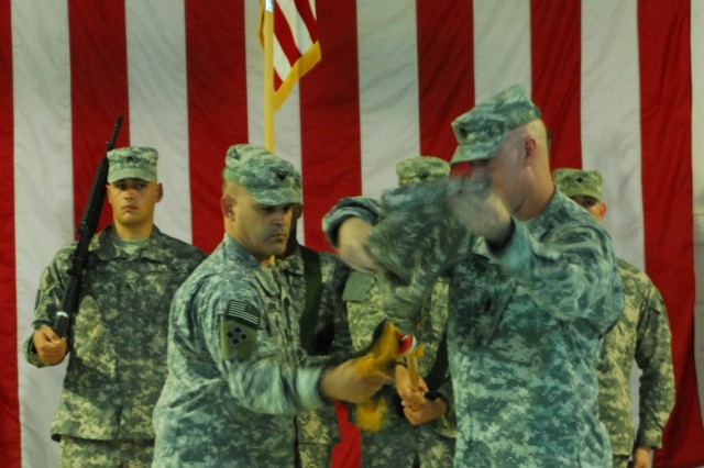 Colonel Lou Lartigue and Command Sgt. Maj. Joseph Altman, 4/3 AAB commander and senior enlisted advisor, uncase the Vanguard Brigade colors during a transfer of authority ceremony at Camp Ramadi, Iraq, Aug. 2.
