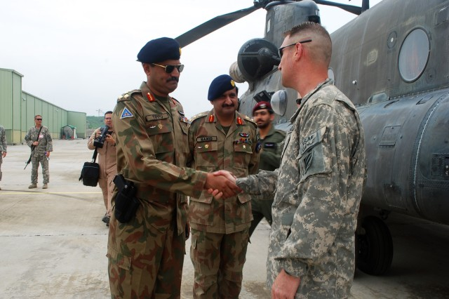 Col. Don Galli, commander of the 3rd Combat Aviation Brigade, Task Force Falcon, greets Pakistan Brig. Gen. Tippu Javed, base commander of Qasim, a base near Rawalpindi, Pakistan, after arriving Aug. 9.