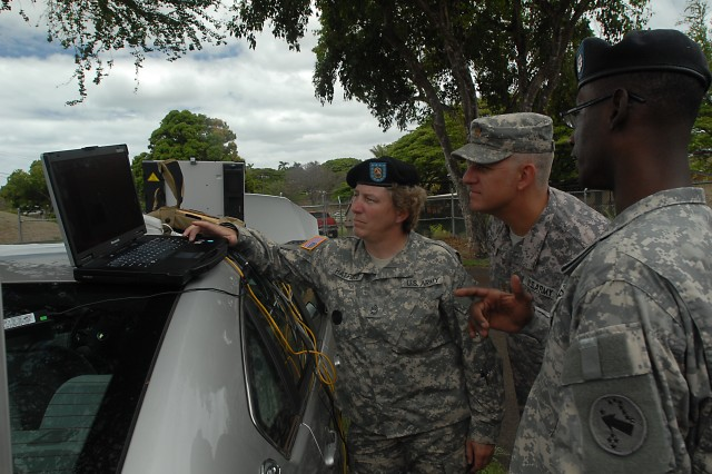 FORT SHAFTER, Hawaii (August 9, 2010) -- U.S. Army, Pacific Contingency Command Post Aviation Officer, Maj. Keegan Leonard,  (center) observes as Sgt. First Class Colleen Hatfield (left), 565th Engineer Detachment and Sgt. First Class Terrance McKinney, U.S. Army, Pacific, CCP engineer, demonstrate the capabilities of the Telecommunications Engineering Equipment/Deployed, a portable communications device which includes an internet connection, telephone and video teleconferencing capabilities.