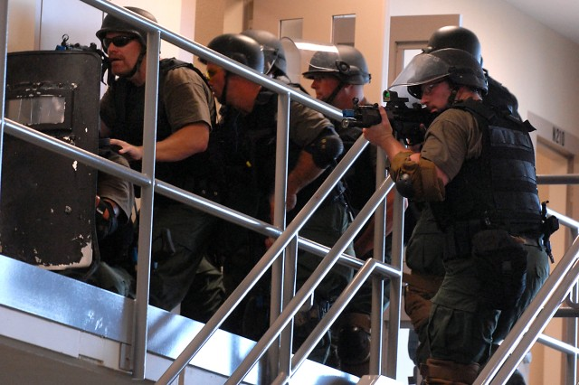 Members of the U.S. Penitentiary's Special Operations Response Team clear rooms in a housing unit with Fort Leavenworth's Special Reaction Team, part of the Correctional Emergency Response Team, during training Aug. 10 at the new Joint Regional Correctional Facility. About 150 law enforcement officials from the Federal Bureau of Prisons participated in the three-day joint tactical training. Other participating teams included those from the Federal Correctional Complex, Florence, Colo.; Federal Correctional Institution, Greenville, Ill.; U.S. Medical Center for Federal Prisoners, Springfield, Mo.; Federal Medical Center, Rochester, Minn.; Federal Correctional Institution, Oxford, Wis.; and Federal Correctional Complex, Terre Haute, Ind.