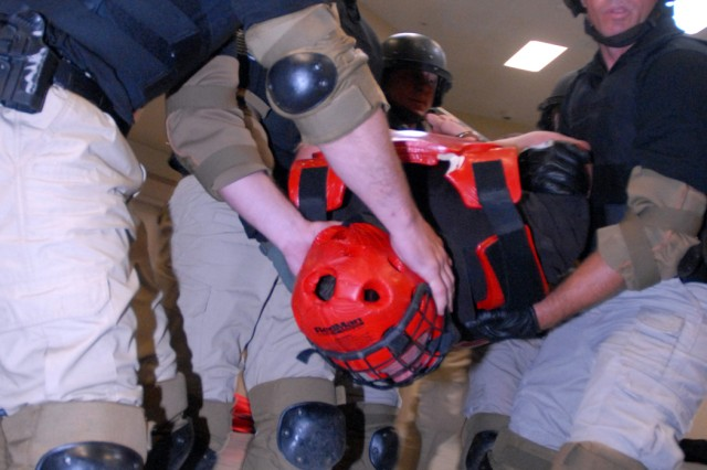 Florence, Colo., Federal Correctional Complex Special Operations Response Team members D. Hand, K. Bolton, J. Doerer, D. Arguello and T. Holcomb, remove their team leader Lt. Sean Janson, portraying an unruly inmate, from his cell during a five-man calculated use of force training scenario Aug. 10 at the new Joint Regional Correctional Facility at Fort Leavenworth, Kan. Other participating teams included those from Fort Leavenworth's Special Reaction Team, part of the Correctional Emergency Response Team; U.S. Penitentiary, Leavenworth, Kan.; Federal Correctional Institution, Greenville, Ill.; U.S. Medical Center for Federal Prisoners, Springfield, Mo.; Federal Medical Center, Rochester, Minn.; Federal Correctional Institution, Oxford, Wis.; and Federal Correctional Complex, Terre Haute, Ind.