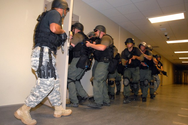 Staff Sgt. Alejandro Gutierrez, Headquarters and Headquarters Company, U.S. Disciplinary Barracks, holds the door as the rest of his Special Reaction Team and the U.S. Penitentiary's Special Operations Response Team enters a housing unit during training Aug. 10 at the Joint Regional Correctional Facility at Fort Leavenworth, Kan. The training not only benefits the teams, but also helps identify anything in the facility that needs addressed before inmates begin arriving in a few months. The 464-inmate capacity, medium- and minimum-security facility will receive about 80 inmates from Fort Sill, Okla., in October and more in November.