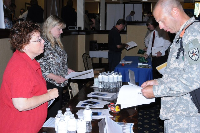 CW5 Ralph Gilgenast talks with Debbie Henkes, a Med-Trans Air Medical Transport representative, at the seventh annual Fort Rucker Job Fair Aug. 10 at The Landing. Gilgenast is retiring soon after 30 years in the military and said he attended the fair to help ease his transition into the civilian workforce.