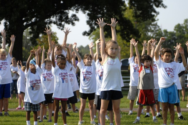 Children of Fort Bragg and Pope Air Force Base active and retired servicemembers perform warm-up drill before competing in the 11th annual Armed Services YMCA Olympics Saturday at the Polo Fields