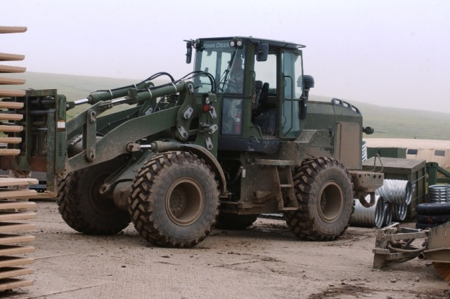 A heavy forklift moves pallets of Durabase mats, used to build a road across the tundra, Camp Mertarvik, Alaska. Each mat weighs more than 1,000 pounds.