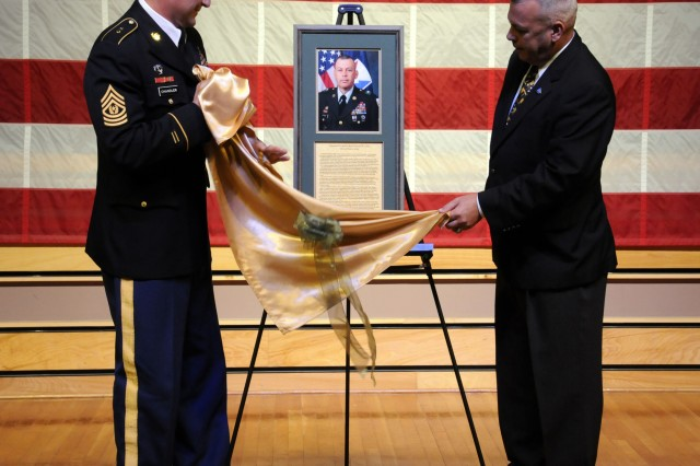 Retired Command Sgt. Maj. Daniel K. Elder and Command Sgt. Maj. Raymond Chandler, United States Army Sergeants Major Academy commandant, unveil Elder's Hall of Honor photo during a ceremony Aug. 12 in the academy's East Auditorium.