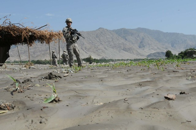 KUNAR PROVINCE, Afghanistan - U.S. Army Cpl. Levi Day, Kunar Provincial Reconstruction Team security forces, stands on a corn field destroyed by flooding from the Kunar River near the Pashad Bridge here July 31. The Kunar Provincial Reconstruction Team visited four bridges during a damage assessment after flooding had occurred in the area.  (Photo by U.S. Air Force Staff Sgt. Nathan Lipscomb, Kunar Provincial Reconstruction Team)