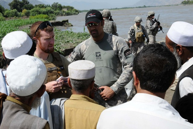 KUNAR PROVINCE, Afghanistan - Paul Negley (Left), the Kunar Province U.S. Agency for International Development representative, talks with locals affected by the flooding near the Pashad Bridge here July 31. The Kunar Provincial Reconstruction Team visited four bridges during a damage assessment after flooding had occurred in the area.  (Photo by U.S. Air Force Staff Sgt. Nathan Lipscomb, Kunar Provincial Reconstruction Team)