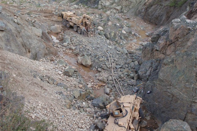 A vehicle recovery crew from Company B, 626th Brigade Support Battalion, 3rd Brigade, 101st Airborne Division adjusts the cabling and ropes connecting their wrecker to a mine-resistant, ambush-protected vehicle that had rolled off a steep mountain pass and lodged against a rock formation approximately 50-feet below. The recovery took the team four-days.  (Photo courtesy of the U.S. Army)
