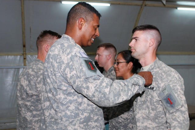 Maj. Gen. Vincent Brooks, the 1st Infantry Division commanding general, places the Army Commendation medal on Sgt. Joshua Read, a fire support sergeant with the 1st Inf. Div., during an awards ceremony at the Contingency Operating Base Basra Town Hall Aug. 8.