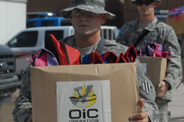 Pfc. Chris Wingate (left), with Battery A, 1st Battalion, 76th Field Artillery Regiment, 4th Advise and Assist Brigade, 3rd Infantry Division, brings donated items to the Anbar Police Department Aug. 10 before an Iraqi Police-hosted community outreach event.