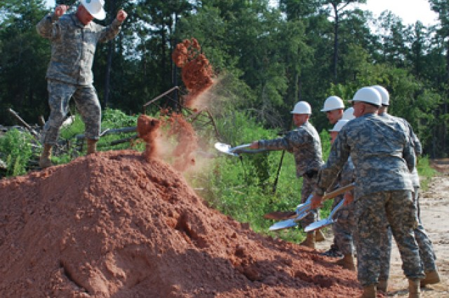 Col. Francis Burns, Fort Polk's garrison commander, stands atop a mound of dirt that is to be symbolically broken for the Warrior Transition Unit barracks on Third Street Aug. 9. His headgear, though shaped like a Stetson, is actually a hard hat.