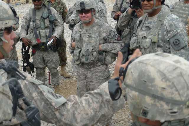 Command Sgt. Maj. Michael T. Hall, center, listens to a pre-mission briefing at Forward Operating Base Lagman, Afghanistan, by a 2nd Stryker Cavalry Regiment Soldier on Aug. 6, 2010, during a battlefield circulation in Regional Command South.