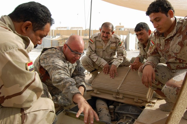 Sgt. John Dunmeyer, second from left, with Company D, 3rd Battalion, 69th Armor Regiment, 1st Advise and Assist Brigade, 3rd Infantry Division, shows Iraqi Army Soldiers how to perform preventive maintenance checks and services on the M1A1 Abrams Main Battle Tank Aug. 3 at Joint Security Station Al Rashid, Iraq. Twelve new IA Soldiers and leaders are attending a two and one-half-week U.S. forces-led tank familiarization course.
