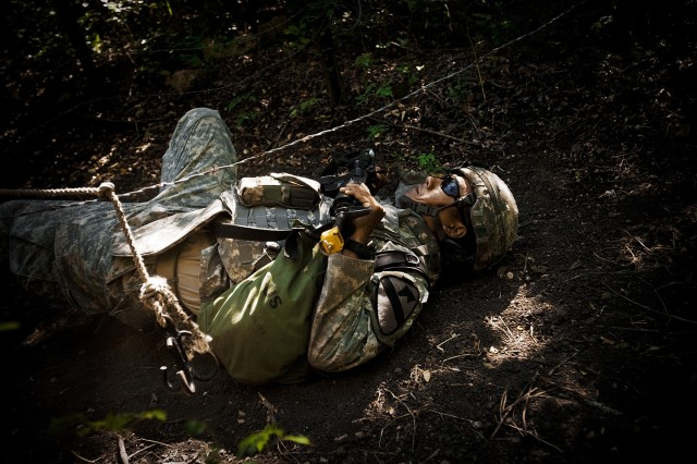 FORT HOOD, Texas-Spc. Jeffrey Santos, from Killeen, Texas, a medical supply Soldier with 1st Brigade Combat Team, 1st Cavalry Division, negotiates his way through a barbed wire obstacle on the warrior skills lane during the 1st Cav. Div. Expert Field Medical Badge Competition, Aug. 10