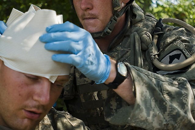 FORT HOOD, Texas-Freemont, Calif. Native, Sgt. Nathaniel Fielding, a medical supply sergeant with 2nd Brigade Combat Team, 1st Cavalry Division, attends to his simulated casualty during the 1st Cav. Div.'s Expert Field Medical Badge Competition, Aug. 12.