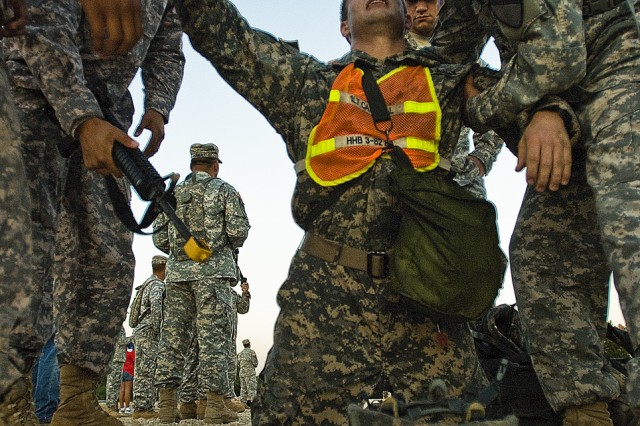 FORT HOOD, Texas-An Expert Field Medical Badge candidate collapses from exhaustion following a 12 mile ruck march during the 1st Cavalry Division's EFMB Competition, Aug. 13.