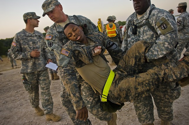 FORT HOOD, Texas-An Expert Field Medical Badge candidate from the 1st Cavalry Division is carried to the aid station after collapsing immediately following a 12 mile ruck march, here, Aug. 13.