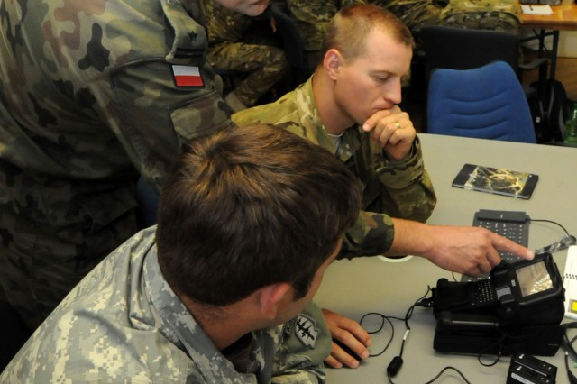 An intelligence officer assigned to Poland Special Operations Command, standing, translates to a Polish intel officer, center, how to use the Secure Electronic Enrollment Kit as a U.S. military intelligence noncommissioned officer assigned to 1st Battalion, 10th Special Forces Group (Airborne), looks on during a training engagement sponsored by U.S. Special Operations Command Europe Aug. 11 at Panzer Barracks. The engagement is part of SOCEUR's mission to increase the SOF interoperability and capability of partner nations within European Command's area of responsibility.