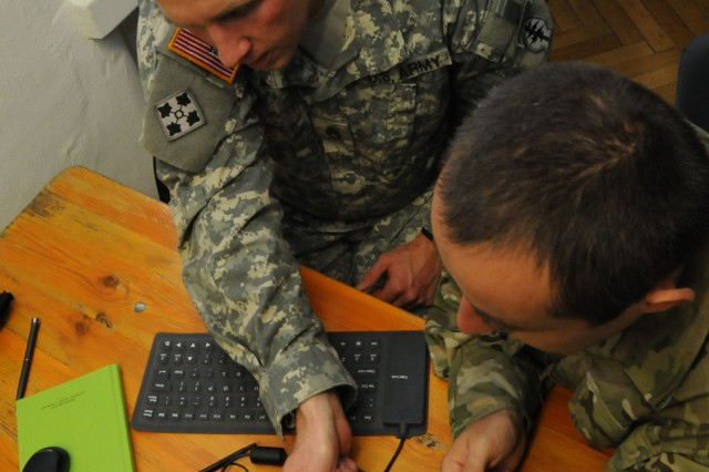 A U.S. military intelligence noncommissioned officer assigned to 1st Battalion, 10th Special Forces Group (Airborne), left, demonstrates how to use the Secure Electronic Enrollment Kit to an intel officer assigned to the Poland Special Operations Command during a training engagement sponsored by U.S. Special Operations Command Europe Aug. 11 at Panzer Barracks. The engagement is part of SOCEUR's mission to increase the SOF interoperability and capability of partner nations within European Command's area of responsibility.
