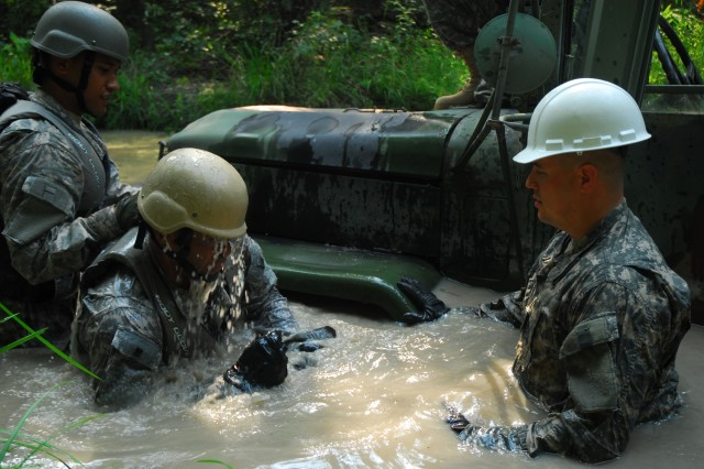 Staff Sgt. Charles Weston, right, an instructor with the Vehicle Recovery Course, observes as a student comes up for air with a handful of mud. The mud is used to estimate the mire factor of the stuck vehicle.